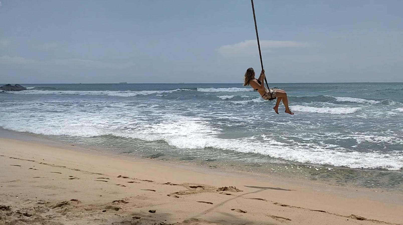 Frau schwingt auf einer Schaukel am Strand hoch über den Wellen des Meeres.