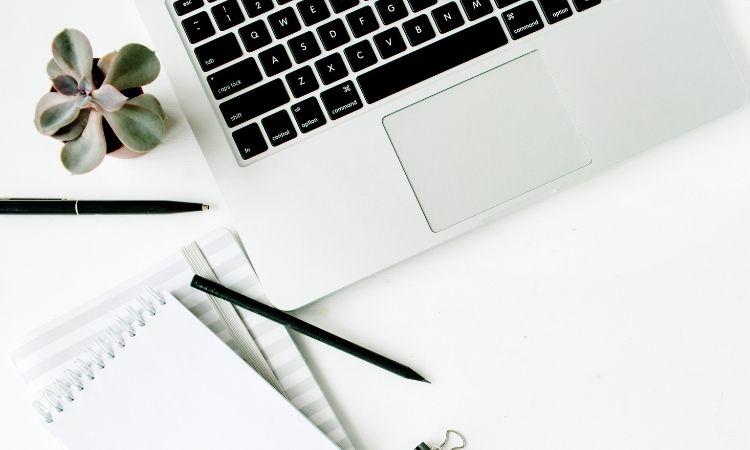 Laptop, Blöcke und Stifte liegen auf einem Schreibtisch